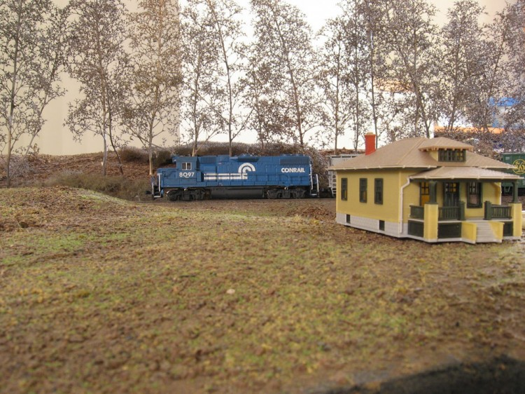 A Conrail GP38-2 Rolls Past The Farm House on the Apartment Door Layout